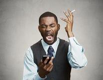 Exécutif fâché soumis à une contrainte tenant le téléphone et la cigarette futés, scre photo libre de droits