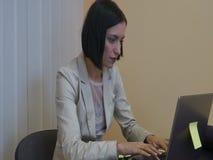 Exécutif féminin sérieux trouvant des idées tout en travaillant à son bureau avec l'ordinateur portable banque de vidéos