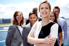 Exécutif femelle blanc se tenant devant des collègues Photographie stock libre de droits