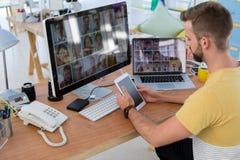 Exécutif masculin à l'aide du comprimé numérique au bureau image stock