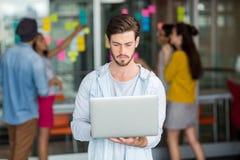 Exécutif masculin attentif à l'aide de l'ordinateur portable Photo libre de droits