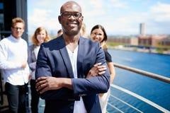 Exécutif masculin noir se tenant devant des collègues Photos stock