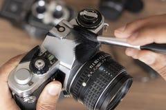 Exécution du nettoyage de la caméra de photo de cru photographie stock