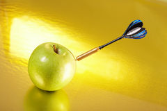 Exact hit of a dart in an apple Stock Photos