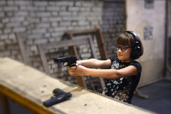 Exact hit in the purpose. Girl shoots a pistol in the shooting gallery Royalty Free Stock Photo