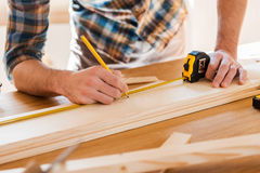 Exact measured. Close-up of young male carpenter making measurements on the wooden plank stock images