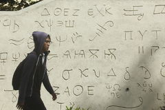 Exact symbols. Student in Sebelasa Maret University walking beside exact symbols royalty free stock image