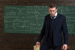 Exacting teacher. Teacher formal wear and glasses looks smart, chalkboard background. Professor exacting and strict royalty free stock photography