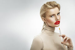 Exaggerated injection to the lips of a beautiful blonde Royalty Free Stock Images