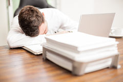 Exahusted businessman sleeping at the office. Portrait of an exhausted young businessman overwhelmed with work and sleeping in the office Royalty Free Stock Images