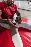 Exakt afrikansk amerikanidrottsman som pressar läka kräm från röret royaltyfri foto
