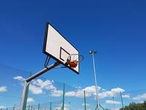 Exakt kast bollen in i basketcirkeln på stadion i den öppna luften på en solig klar dag Basketdomstol i det öppet arkivfoton