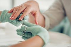 Exakt kompetent spikar förlagen i skyddande gummihandskar som klipper extra hud royaltyfri fotografi