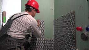 Exakt man med den röda hjälmen som belägger med tegel väggen med keramiska tegelplattor lager videofilmer