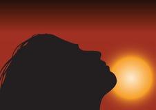 Exalt at dawn. Slhouette of a young girl over the rising sun Stock Photos