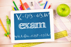 Exam against students desk with tablet pc Royalty Free Stock Image