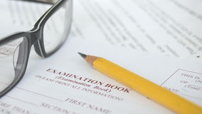Exam Book. A pencil and glasses on top of an examination book stock footage