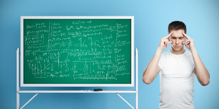 Exam concept. Pensive man standing next to chalkboard with mathematical formulas on blue wall background. Exam concept. 3D Rendering Royalty Free Stock Images