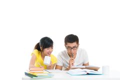 Exam eve. Copy-spaced image of two fellow students poring over books stock photo
