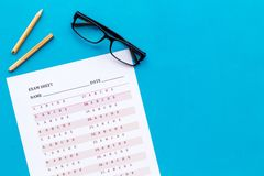 On the exam. Exam sheet, answer near glasses and pencil on blue background top view copy space. On the exam. Exam sheet, answer near glasses and pencil on blue royalty free stock photos