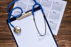 Exam pad, stethoscope and calendar on the smooth wooden table stock photo