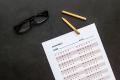On the exam. Exam sheet, answer near glasses and pencil on black background top view.  stock image