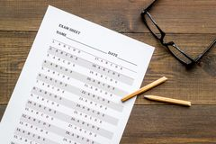 On the exam. Exam sheet, answer near glasses and pencil on dark wooden background top view.  royalty free stock photo
