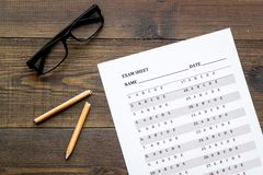 On the exam. Exam sheet, answer near glasses and pencil on dark wooden background top view.  stock photography