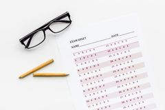 On the exam. Exam sheet, answer near glasses and pencil on white background top view.  stock photography