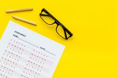 On the exam. Exam sheet, answer near glasses and pencil on yellow background top view copy space. On the exam. Exam sheet, answer near glasses and pencil on royalty free stock photo
