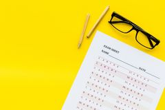 On the exam. Exam sheet, answer near glasses and pencil on yellow background top view space for text. On the exam. Exam sheet, answer near glasses and pencil on stock photo