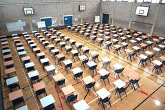 Exam Time. Exam tables and chairs set-up in a huge sports hall ready for exams to be taken stock images