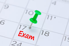 Exam written on  a calendar with a green push pin to remind you Stock Photos