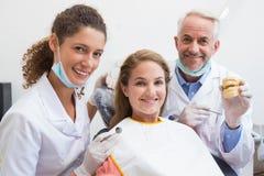 Exame do dentista dentes dos pacientes na cadeira dos dentistas com assistente fotografia de stock royalty free