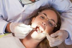Exame do dentista dentes dos pacientes na cadeira dos dentistas sob a luz brilhante fotos de stock