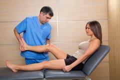 Exame e mobilização do doutor da articulação do joelho à mulher fotografia de stock