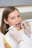 Exame pediatra do dentista dentes das meninas na cadeira dos dentistas Imagens de Stock Royalty Free