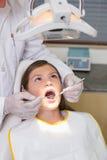 Exame pediatra do dentista dentes dos pacientes na cadeira dos dentistas Fotos de Stock Royalty Free