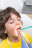 Exame pediatra do dentista dentes dos rapazes pequenos na cadeira dos dentistas Imagem de Stock
