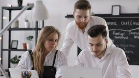 Examen de groupe divers d'hommes d'affaires pour le plan de travail dans le bureau moderne de hippie