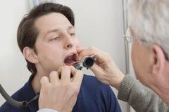 Examen de la garganta con el depresor Imagenes de archivo