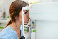 Examen de vue Femme vérifiant la vision d'oeil sur l'équipement d'optométrie photographie stock libre de droits