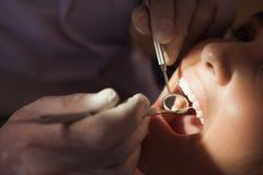Examen del dentista dientes de los pacientes en la silla de los dentistas bajo luz brillante Fotos de archivo