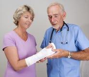 Examen del doctor echado en el brazo de la mujer mayor Imagen de archivo libre de regalías