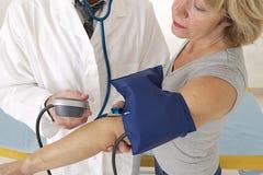 Examen del doctor -- medida de la presión arterial imagenes de archivo