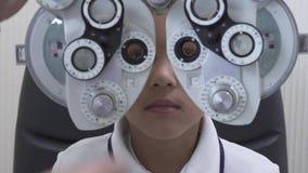 Examen del ojo del ni?o peque?o en el oftalm?logo del optometrista que consume el phoropter cercano Manos del doctor en m?dico bl metrajes