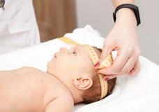 Examen médico infantil - doctor que comprueba contorno de cabeza con un measureme foto de archivo libre de regalías