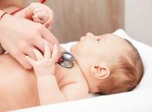 Examen médico infantil - doctor que comprueba golpe y los pulmones de corazón con imagenes de archivo