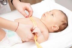 Examen médico infantil - doctor que comprueba tamaño del pecho con un measurem fotografía de archivo