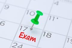 Examen op een kalender met een groene duwspeld die wordt geschreven om u eraan te herinneren Stock Foto's